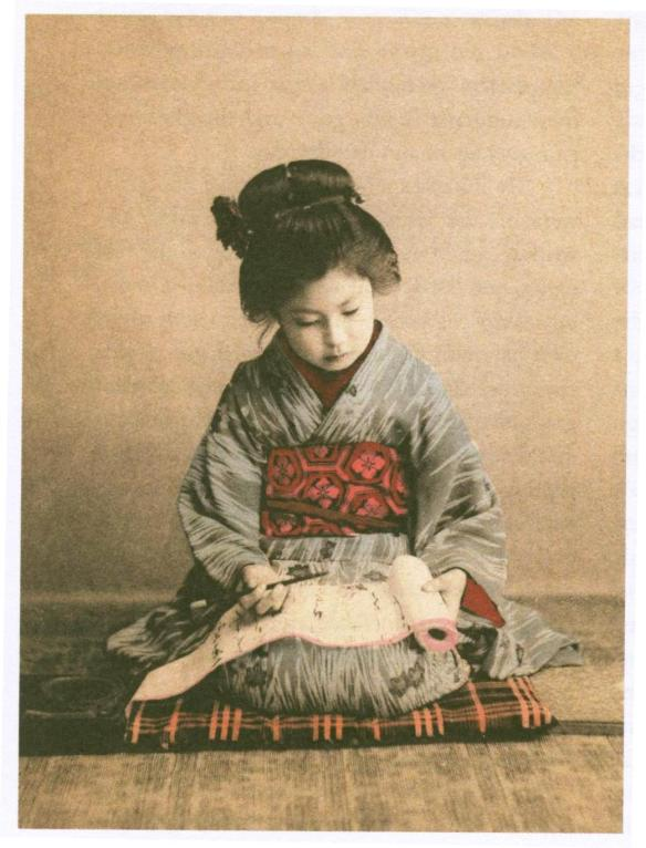 Japanese girl practicing calligraphy, circa 1890