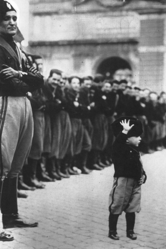 Photo: A uniformed child joins forty thousand teenage Fascists at Rome's Place du Peuple, 1932