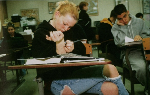 Amy, sixteen, scrawls on her arm during a history class in San Jose, California, 1999. Photograph by Lauren Greenfield